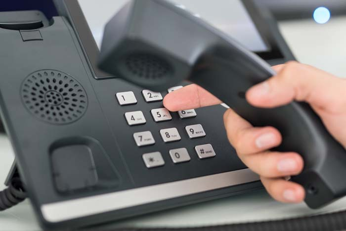 Fingers dialing a number on a deskphone